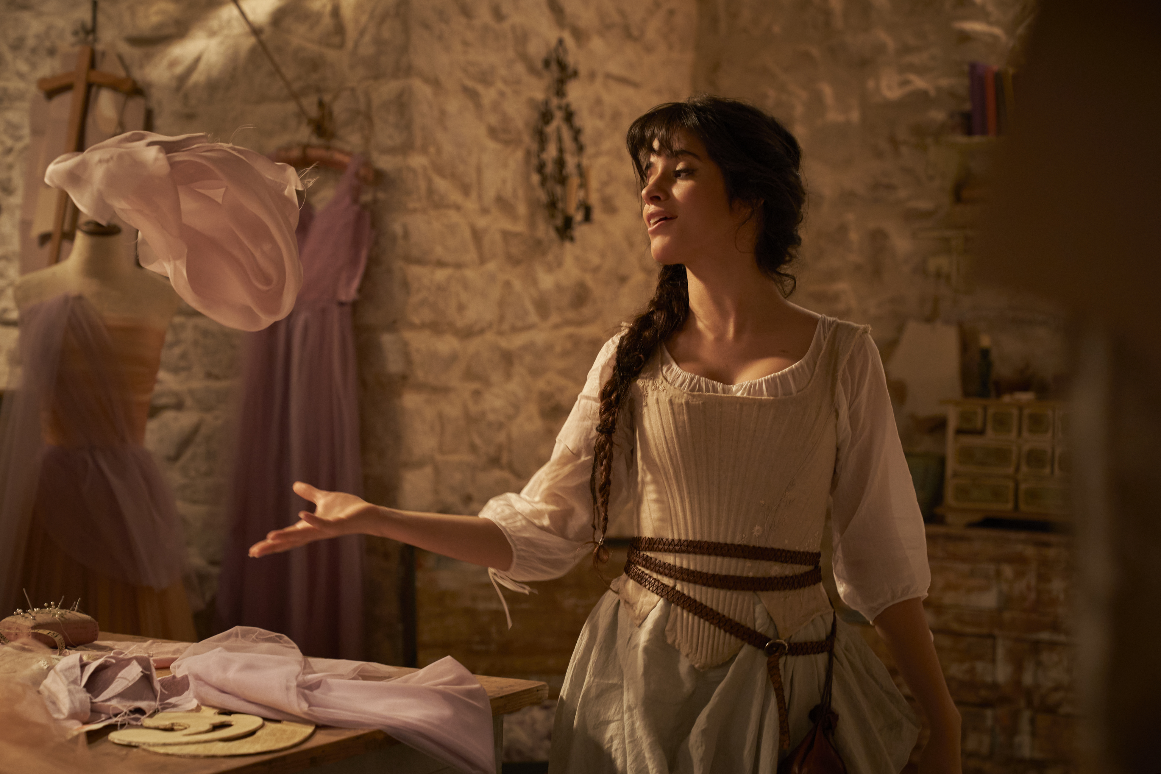 A still from 'Cinderella' (2021) of Camila Cabello as Cinderella dancing and singing to herself