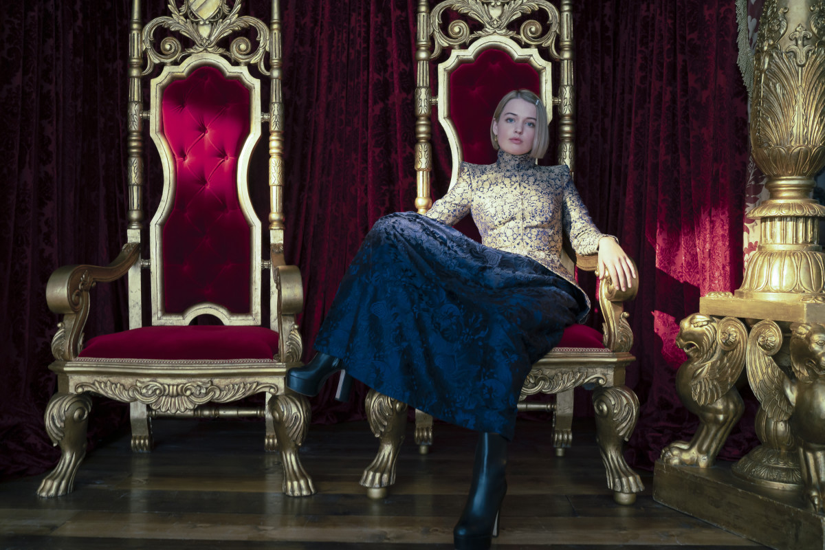A still from 'Cinderella (2021)' of Princess Gwen lounging on the throne