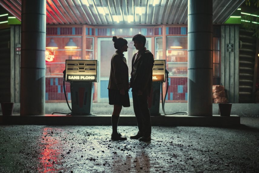 A still from Season 3 of Sex Education of Maeve and Otis standing in the rain at night about to kiss