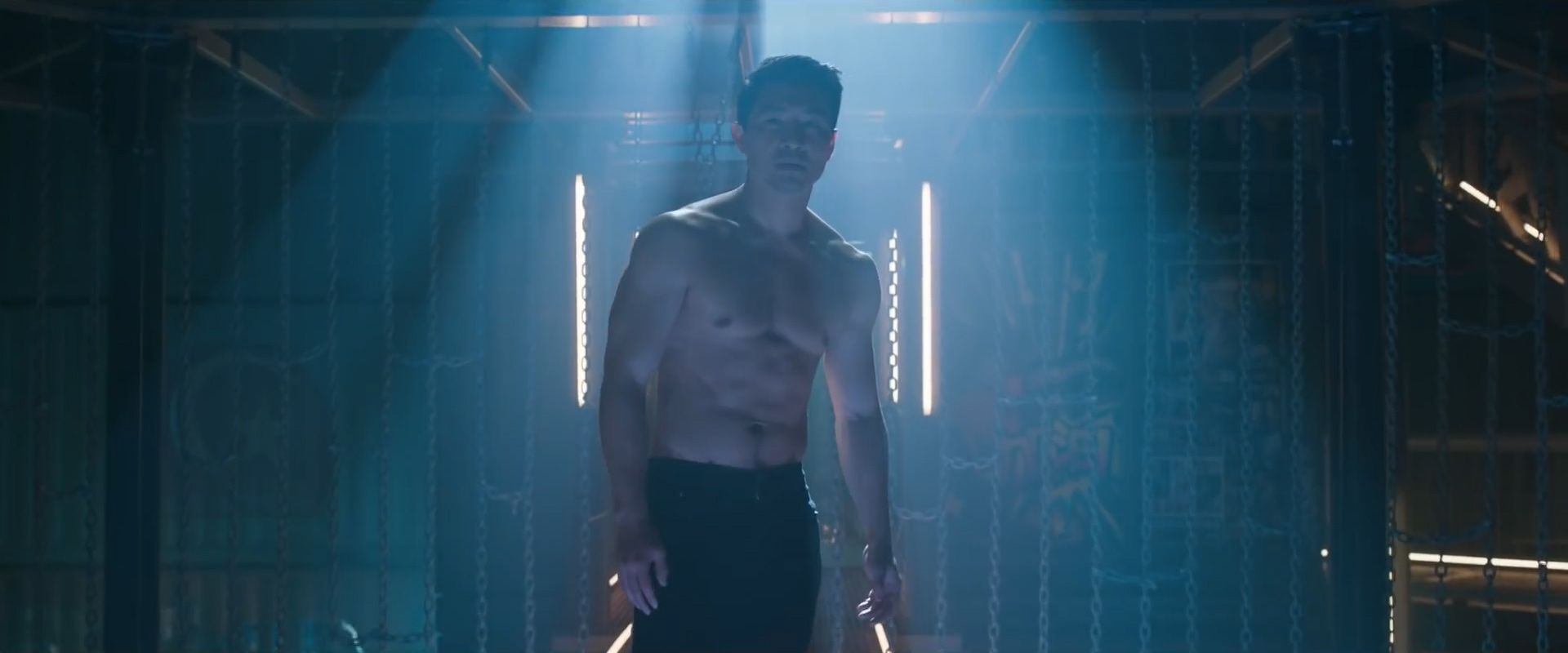 A still from 'Shang-Chi' of shirtless Simu Liu as Shang-Chi emerging from the shadows in the fighting ring