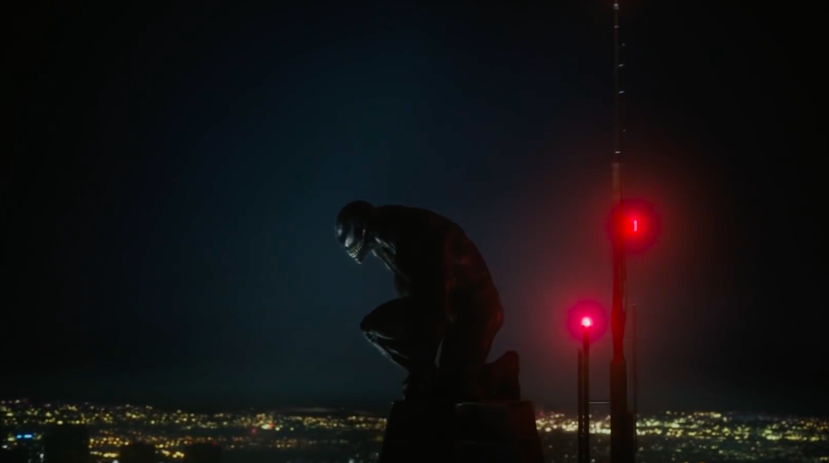 A still of Venom at the top of a tower at night looking down at the city