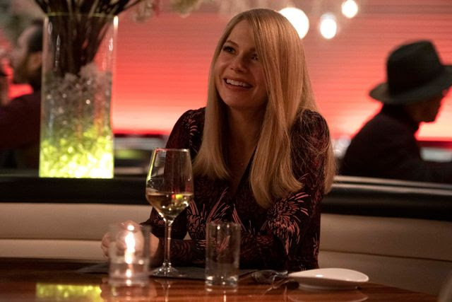 """A still from """"Venom: Let There Be Carnage"""" of Anne smiling in a restaurant"""